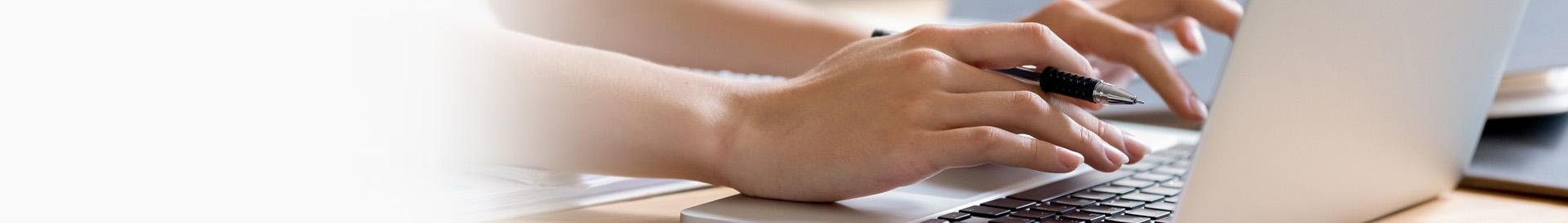 Osoba korzystająca z laptopa z długopisem w ręku